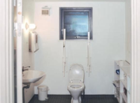Badeværelse med hvide vægge og hvidt sanitet